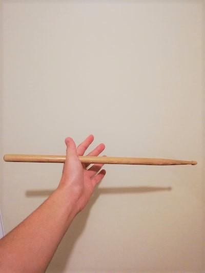 ①スティックを親指と人差し指の間に挟む